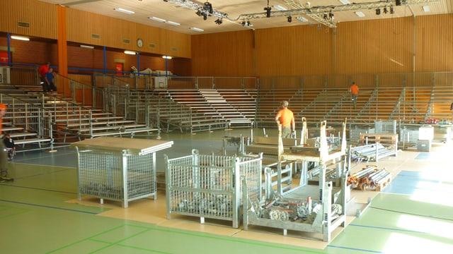 Lavurers vid montar la tribuna en la sala dal center da sport e cultura a Mustér.