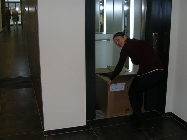 Frau zieht Kartonschachtel aus einem Lift.