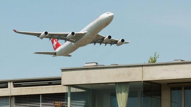 Ein Airbus der Fluggesellschaft Swiss hebt über den Dächern des Glattparks ab