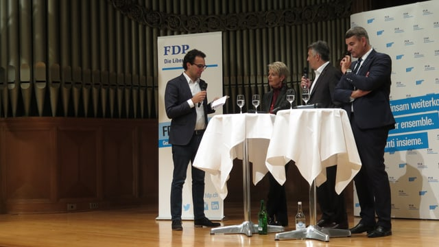 vier Menschen auf Bühne an STehstischen im Gespräch