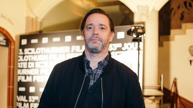 Ein Mann mit grauem Bart vor einer Werbetafel der Solothurner Filmtage.