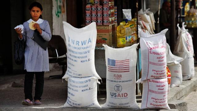 Ein Mädchen mit einem Brot in der Hand steht neben weissen Lebensmittelsäcken mit der Aufschrift «UNRWA» und «USAID».