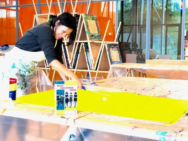 Annette König bepinselt ein grosse Leinwand in einem Atelier.