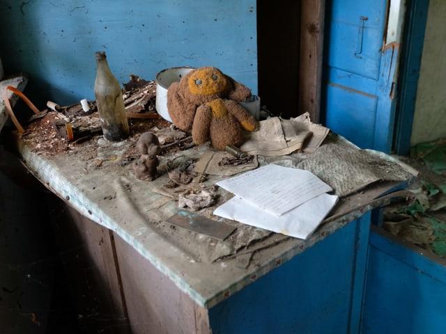 Stofftier liegt auf dem Tisch eines verlassenen Hauses.