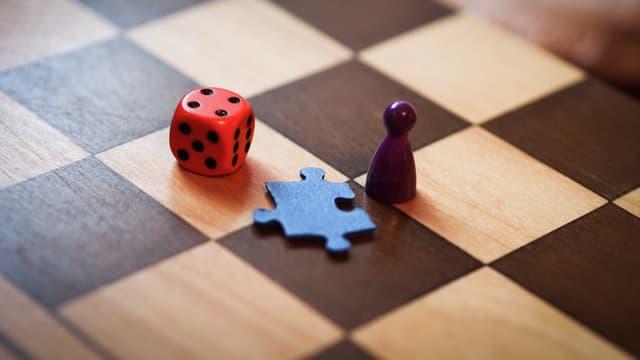 Ein Würfel, ein Puzzleteil und eine Spielfigur auf einem Schachbrett