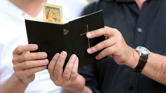 Zwei Männerhände, die gemeinsam ein Gebetsbuch halten.