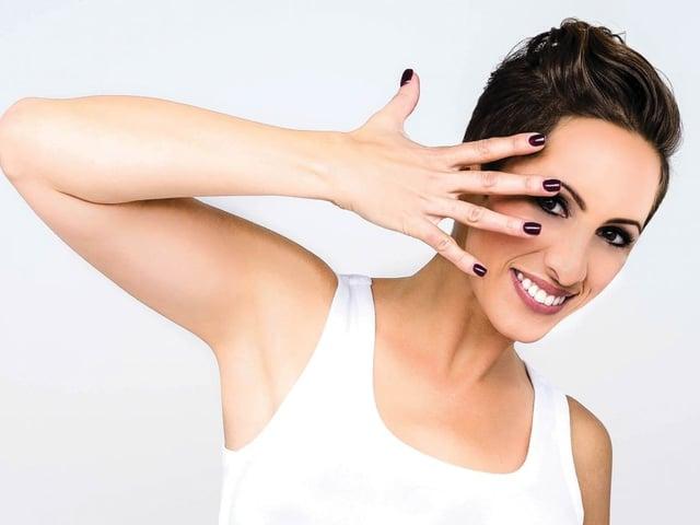Frau mit Handgeste vor dem Gesicht.