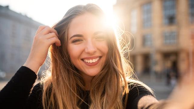 Eine hübsche junge Frau lächelt in die Kamera, die Sonne umspielt ihr Gesicht.