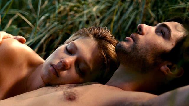 Eine Frau liegt einem Mann in den Armen. Sie liegen im Gras und sind nackt.