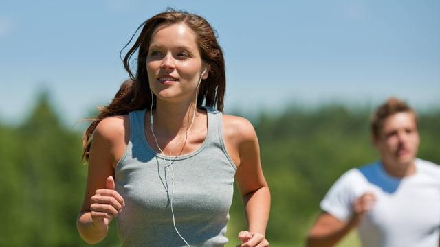 Eine Joggerin mit Kopfhörer rennt vor einem Mann ohne Musik in den Ohren.