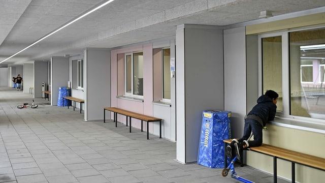 Kind blickt durchs Fenster aus dem innenhof in ein Schlafzimmer des Bundesasylzentrums in Zürich