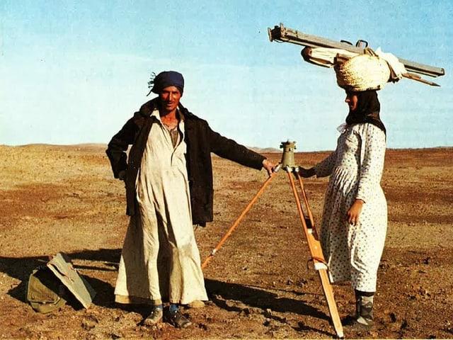 Mann in Wüste mit Messgerät. Frau mit Stativ auf Kopf.