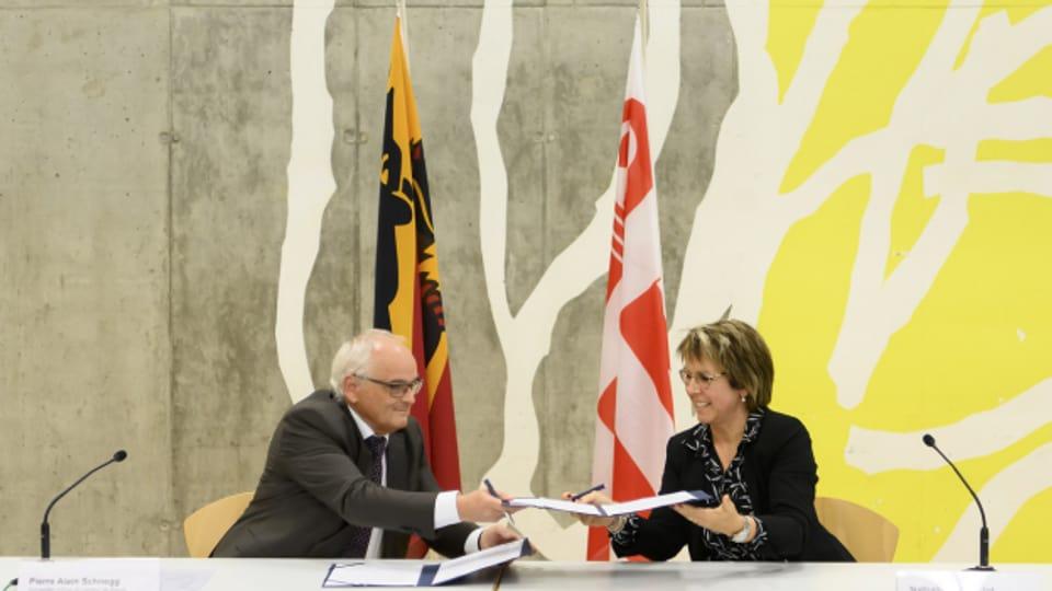 Der Berner Regierungsrat Pierre-Alain Schnegg und seine jurassische Amtskollegin Nathalie Barthoulot tauschen die Erklärung zum Unterschreiben aus