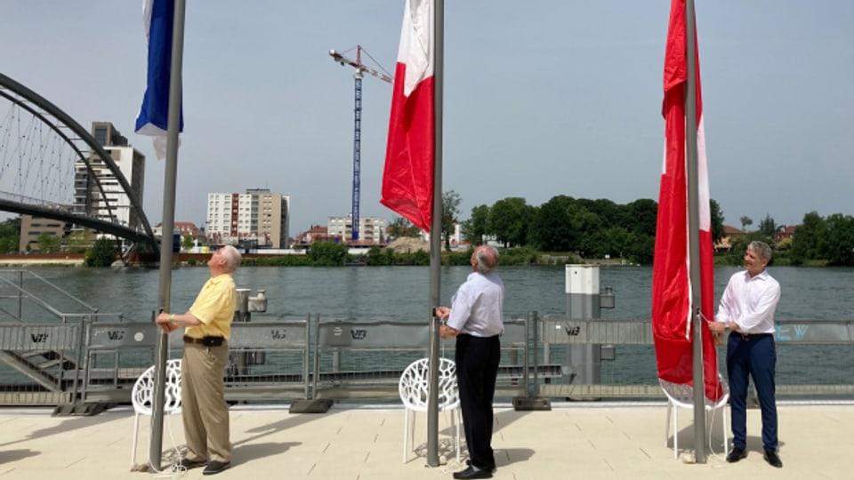 BS-Regierungspräsident Beat Jans und die Bürgermeister von Hunique und Weil (von rechts) hissen zur Eröffnung des Rheinparks Fahnen