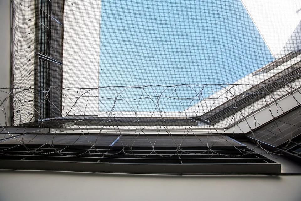 Stacheldraht und Sicherheitsnetze ueber einen Spazierhof des Basler Gefaengnis Waaghof in Basel