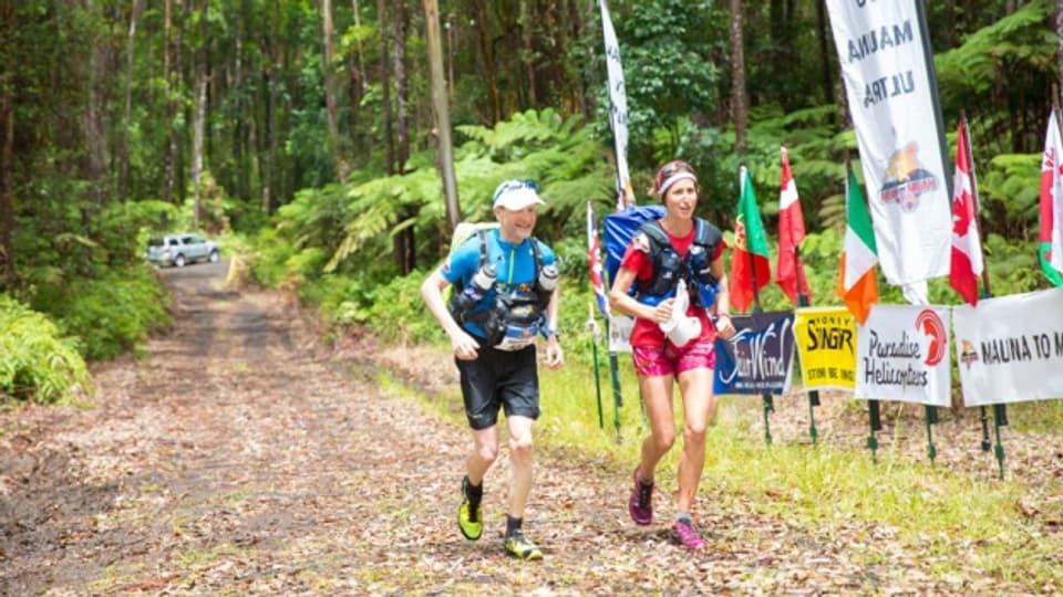 Roberto Rivola und die in Führung liegende Frau laufen ins Ziel der ersten Etappe ein.