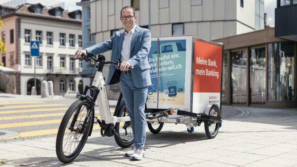 Der Wiler Stadtrat Andreas Breitenmoser posiert mit dem Velo-Grossanhänger.