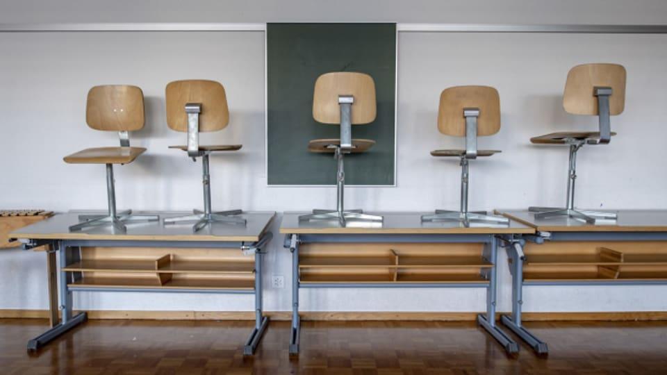 Stühle stehen auf Tischen in einem Klassenzimmer