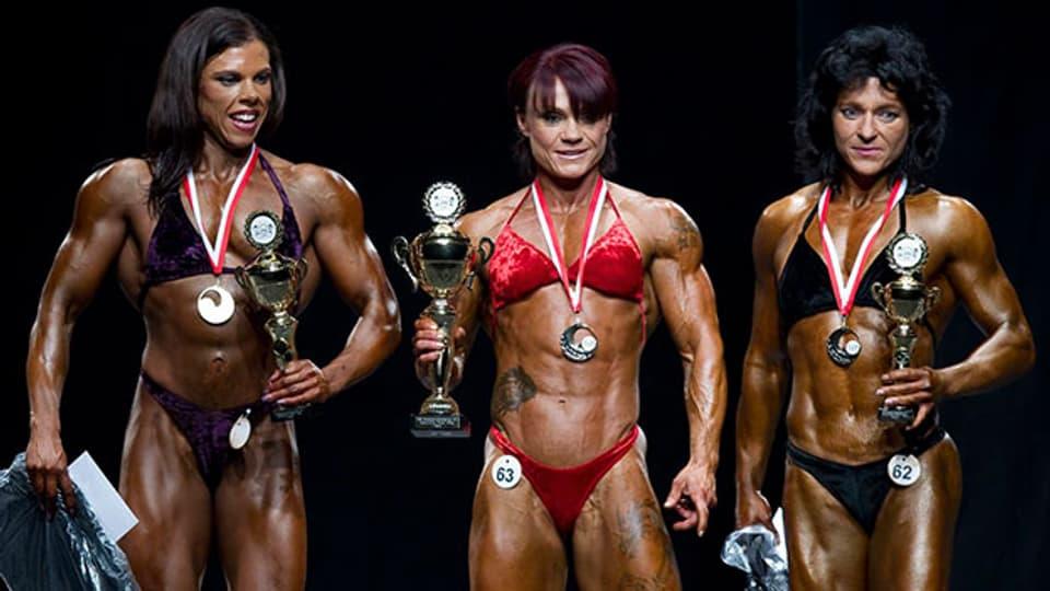 Auf dem Podest der Schweizermeisterschaft im Bodybuilding 2011: Franziska Bossert (l.), Jay Fuchs (m.) und die 3. platzierte Franziska Leuthold (r.).,