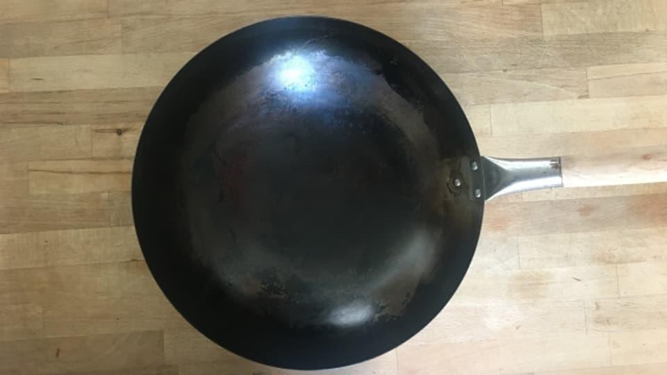 Mit schwarzer Patina überzogen, ist der Wok bereit zum Kochen.