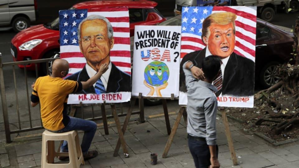 Karikaturen von Biden und Trump auf einer Strasse in Indien.