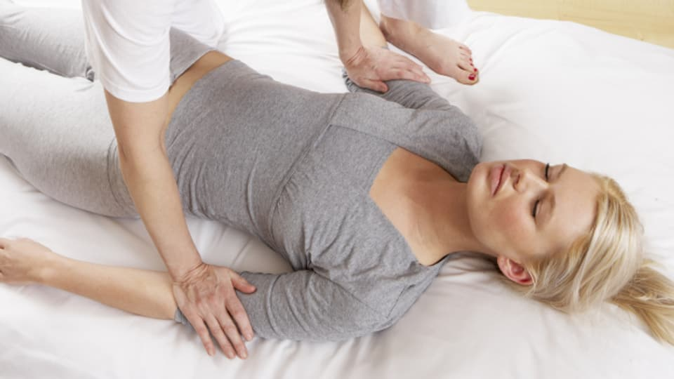 Bei der Atemtherapie ist man angezogen auf der Massageliege und wird durch Berührungen zu tiefem Atmen animiert.