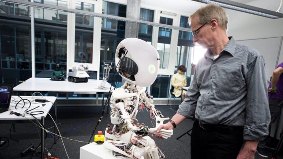 Professor Rolf Pfeifer schüttelt Roboy die Hand, der an der  ETH entwickelt wurde.