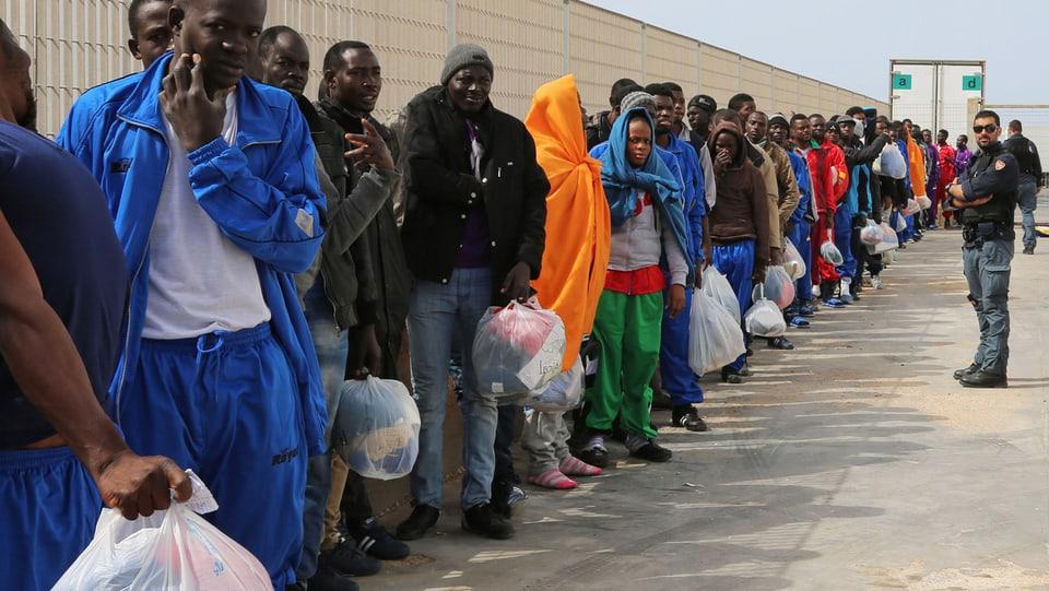 Migranten auf Lampedusa warten auf ein Schiff.