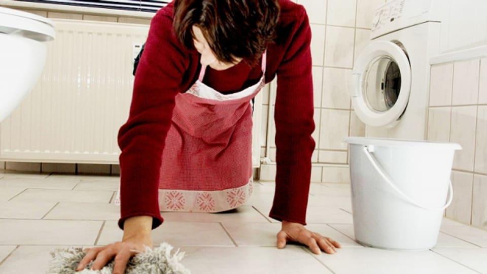 Frau ohne Papiere putzt ein Bad auf den Knien