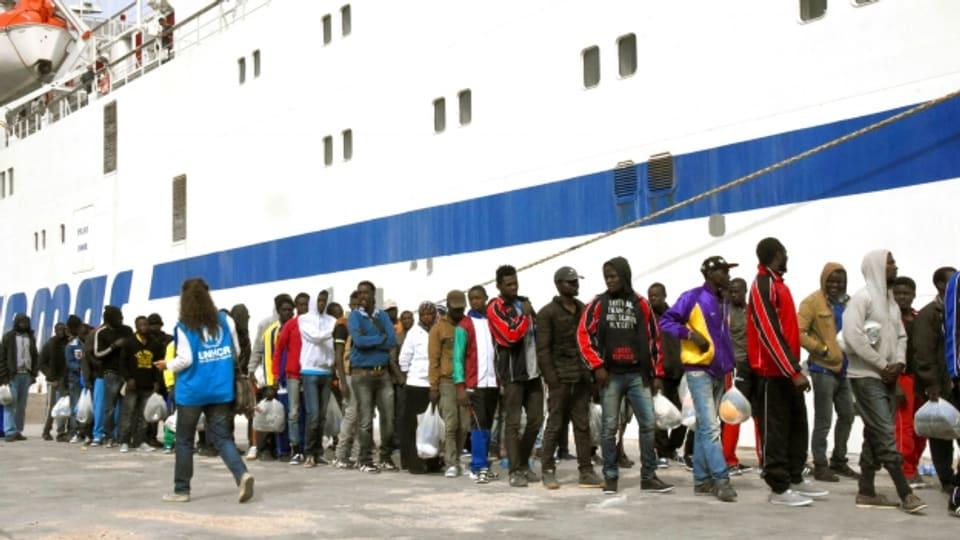 Übers Mittelmeer gekommen: Migranten steigen in Lampedusa auf die Fähre zum Festland