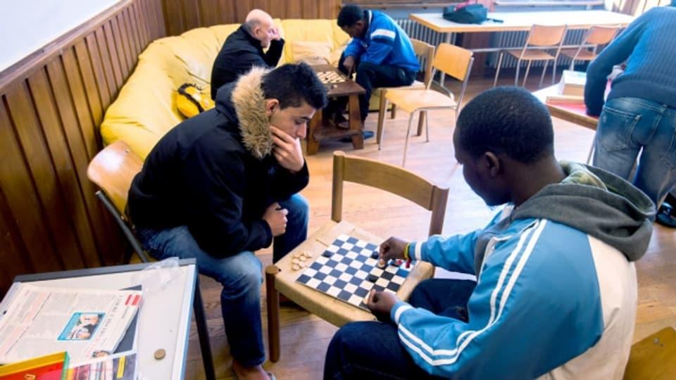 Asylbewerber spielen im Aufenthaltsraum des Asylzentrums Losone Schach.