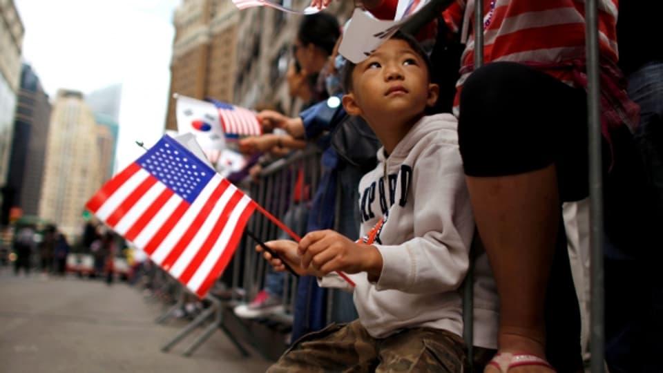 Ein Junge hält bei einer koreanischen Parade in Manhattan die Amerika-Flagge.