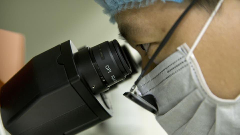 Ein Forscher mit Mundschutz guckt in ein Mikroskop.