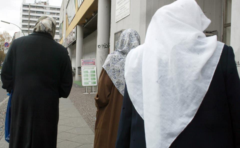 Muslimische Frauen beim Einkaufen in Neukölln. Im Hintergrund ein Firmenschild mit arabischen Schriftzeichen.