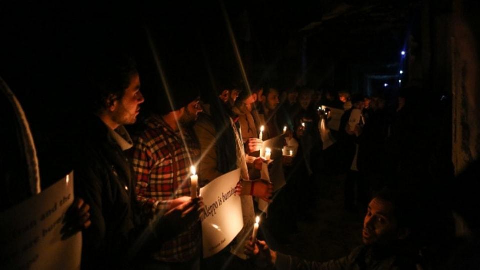 Aktivisten machen mit Kerzen und Plakaten aufmerksam auf die Lage in Aleppo.