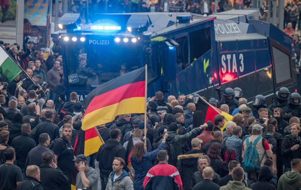 Rechte Demonstranten umringen einen Wasserwerfer