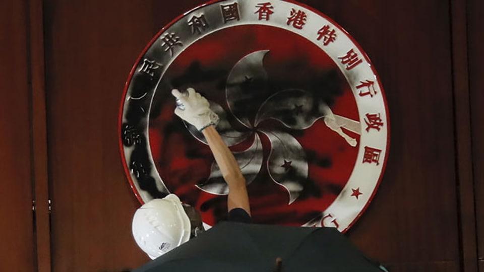 Ein Demonstrant beschmiert das Emblem von Hongkong am 1. Juli 2019.