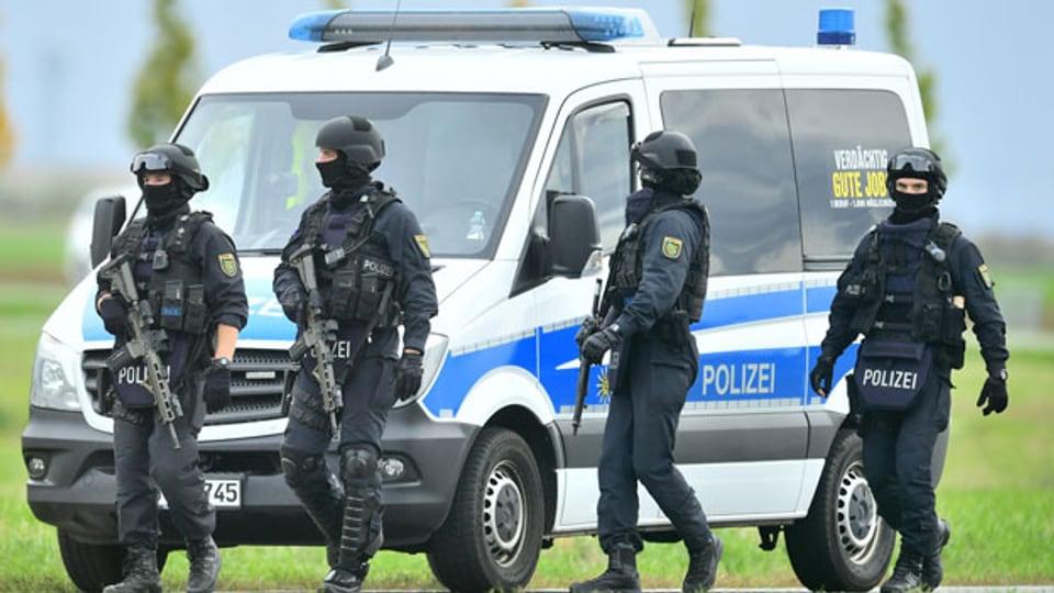 Polizisten in deutschen Halle, wo Schüsse gefallen sind und es offenbar Tote gegeben hat.
