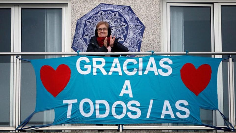 Der allabendliche Applaus ist leiser geworden. Aber verstummt ist er nicht. Hier eine ältere Dame auf ihrem Balkon in La Coruña, im Norden Spaniens.