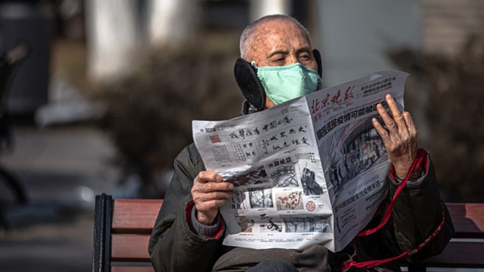 Februar 2020: Ein älterer Herr liest auf einer Parkbank in Peking eine chinesische Zeitung.