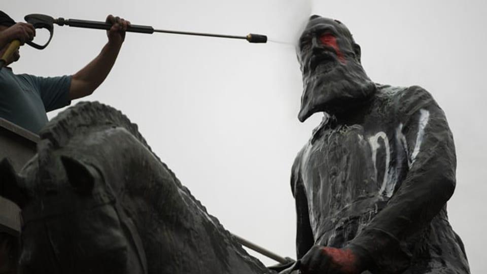 Darf Leopold II weiterhin vor dem Königspalast thronen oder nicht? Ein Mitarbeiter der Stadt Brüssel entfernt im Juni 2020 Graffitis von der Statue.