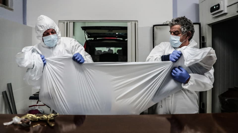 Portugiesische Bestatter in Schutzanzügen halten die Leiche eines Mannes, der im Zusammenhang mit Covid-19 gestorben ist. Portugal hat vergangene Woche die Zahl von 300 coronabedingten Todesfällen an einem Tag überschritten.