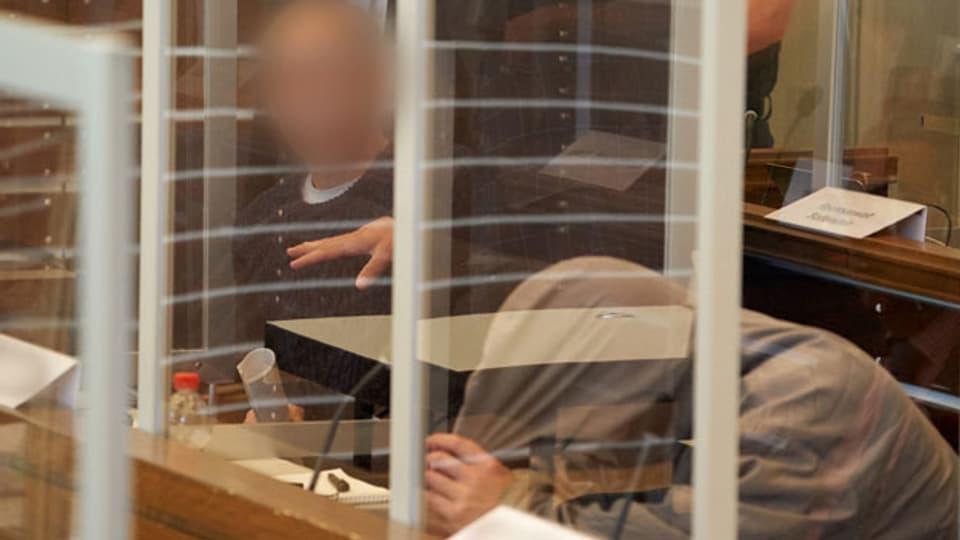 Die beiden Angeklagten Anwar R. (li.) und Eyad A.(re.) auf der Anklagebank des Oberlandesgerichts hinter Corona-Schutzscheiben. Ihnen wird die Beteiligung an syrischer Staatsfolter vorgeworfen. Archivaufnahme vom April 2020.