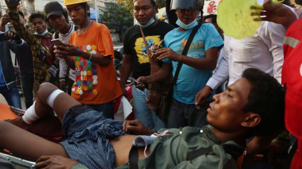 In der Stadt Mandalay wird ein verwundeter Demonstrant weggetragen.