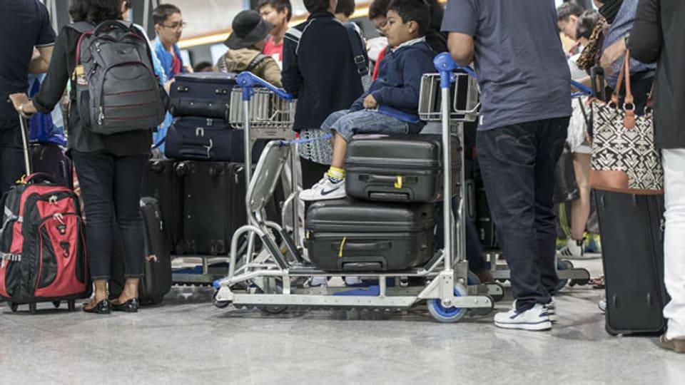 Aufs Fliegen verzichten – aus Umweltschutzgründen? Obwohl die Reise im Zug ist teurer als im Flugzeug? Bild: Passagiere stehen in der Check-in-Halle 2 am Flughafen Zürich an.
