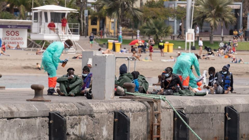 Sanitäterinnen und Sanitäter versorgen Migranten, die mit dem Boot auf Teneriffa angekommen sind.
