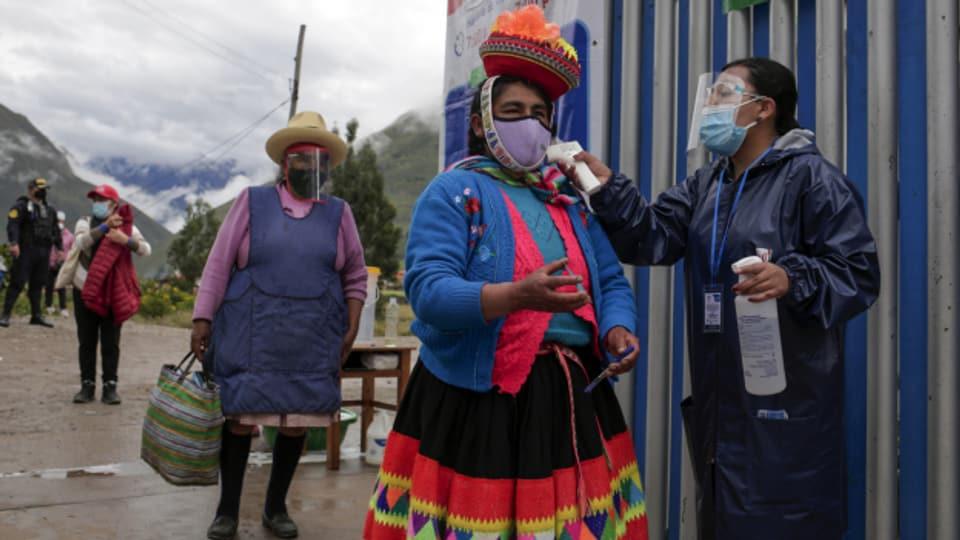 Fiebermessen bei einer Wählerin in Ollantaytambo, Peru.