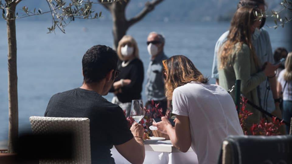 Ein Paar isst auf der Terrasse eines Hotelrestaurants am Seeufer von Ascona am Karfreitag, 2. April 2021.