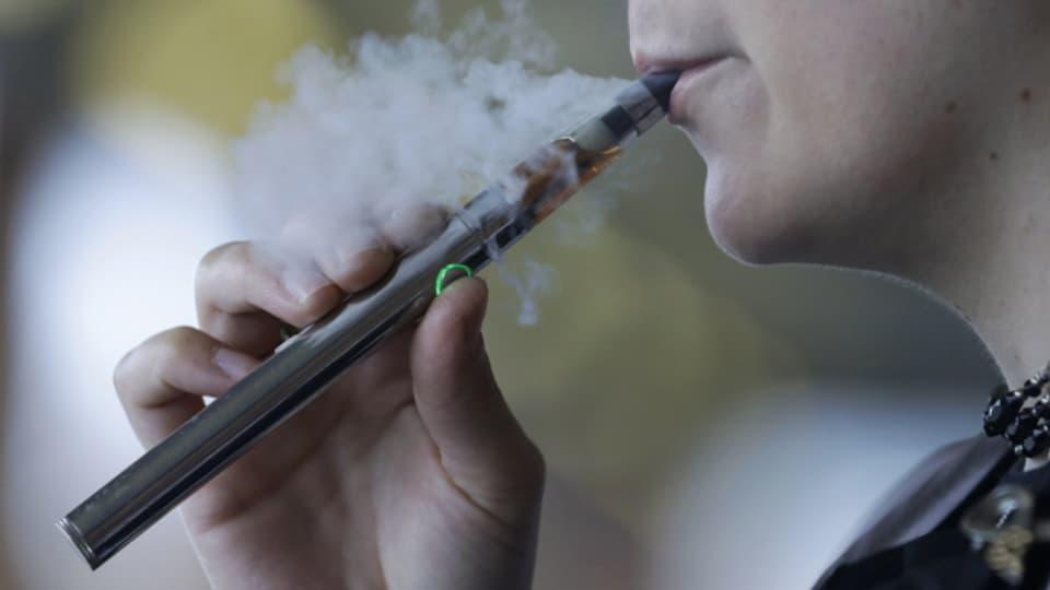 Eine Frau benutzt eine E-Zigarette, auch Vaping-Gerät genannt (Symbolbild).
