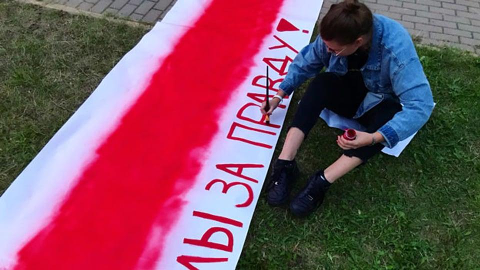 Maria Matusevich bemalt ein Transparent in den Farben der Opposition mit dem Spruch: «Wir sind für die Wahrheit».